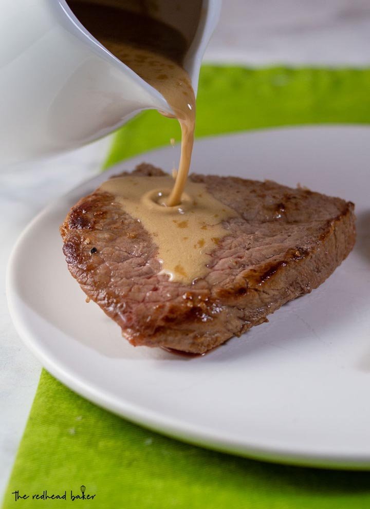 Whiskey sauce being poured onto a piece of steak