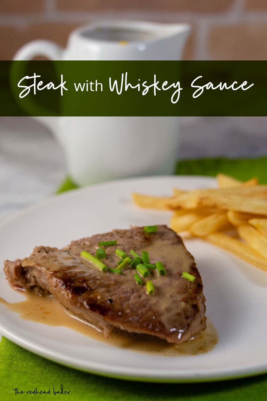 A plate of steak with whiskey sauce and a side of French fries with a container of whiskey sauce in the background