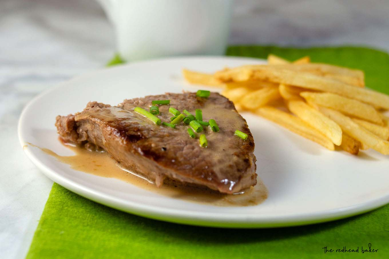 A plate of steak with whiskey sauce and a side of French fries