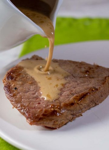 Whiskey sauce being poured onto a piece of sirloin steak