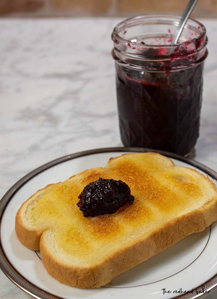 A buttered slice of toast with a dollop of cherry amaretto preserves