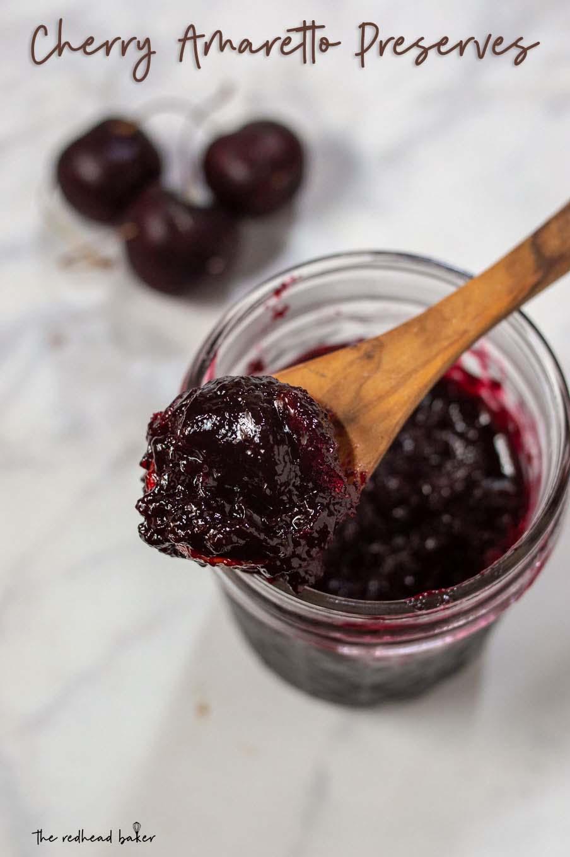An overhead shot of a jar of cherry amaretto preserves