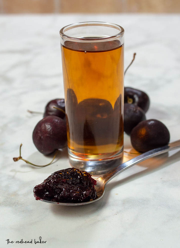 A spoonful of cherry amaretto preserves with a shot glass of amaretto and fresh sweet cherries.