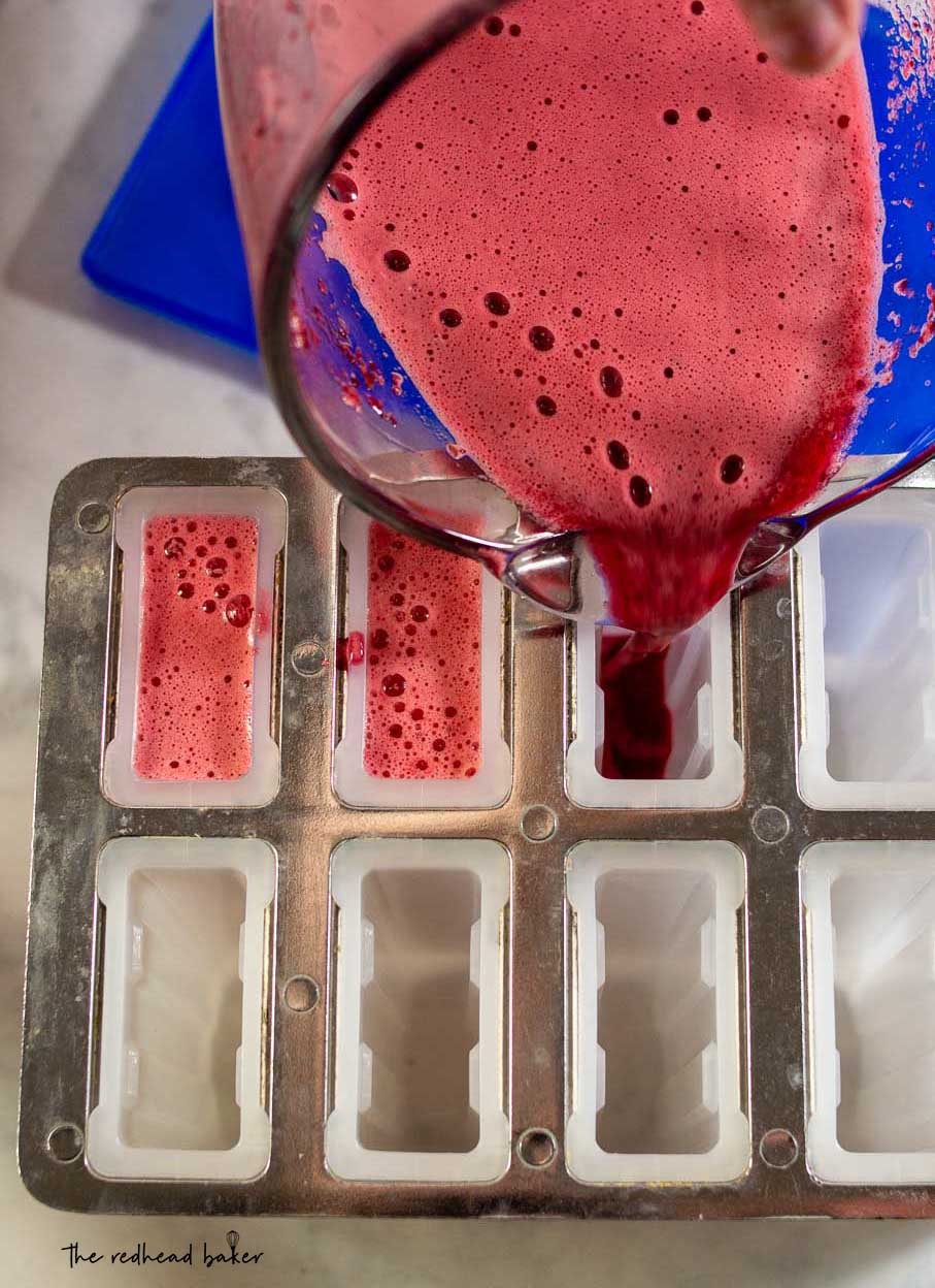 Cherry limeade mixture being poured into a popsicle mold.