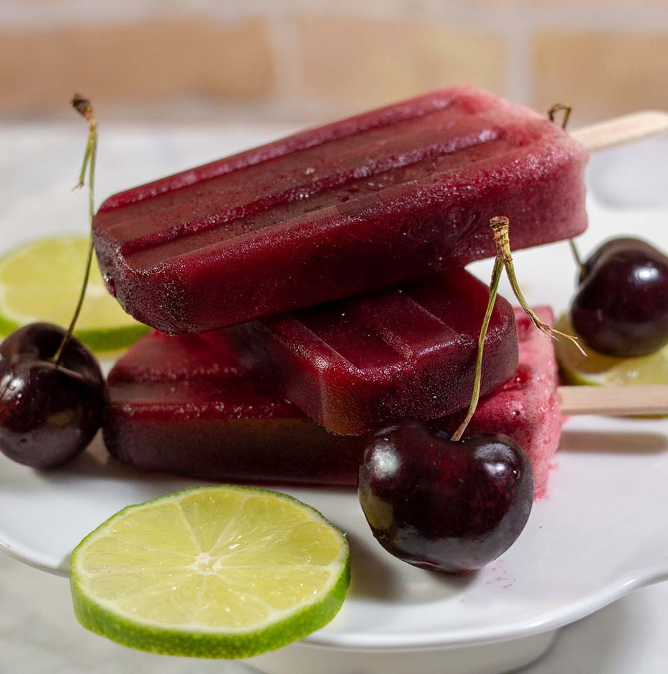 Three cherry limeade pops stacked on top of each other on a mini dessert stand with lime slices and cherries.