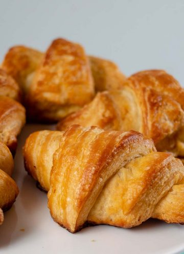 A close-up shot of a plate of mini butter croissants.