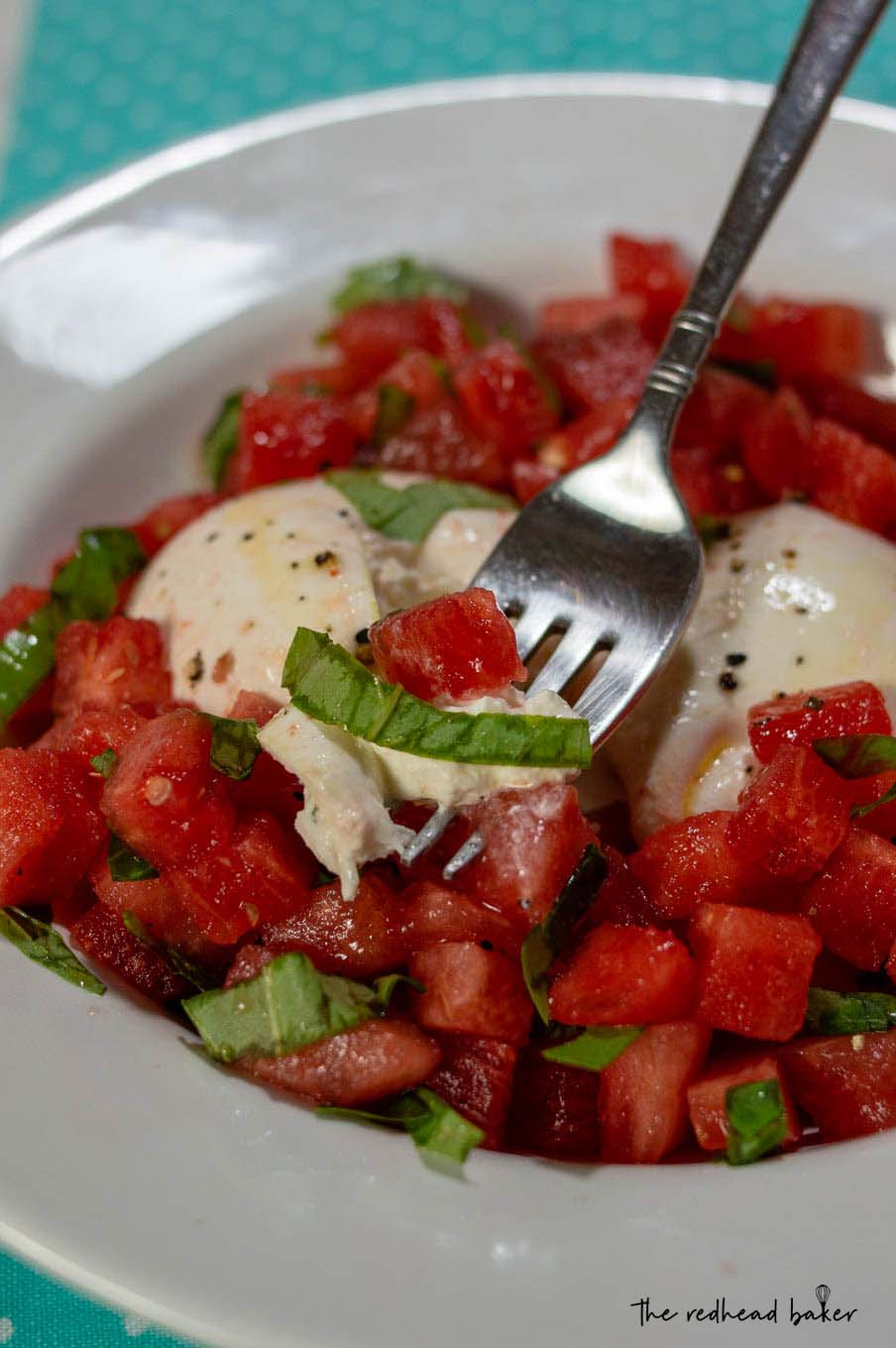 A dish of watermelon burrata salad with a fork