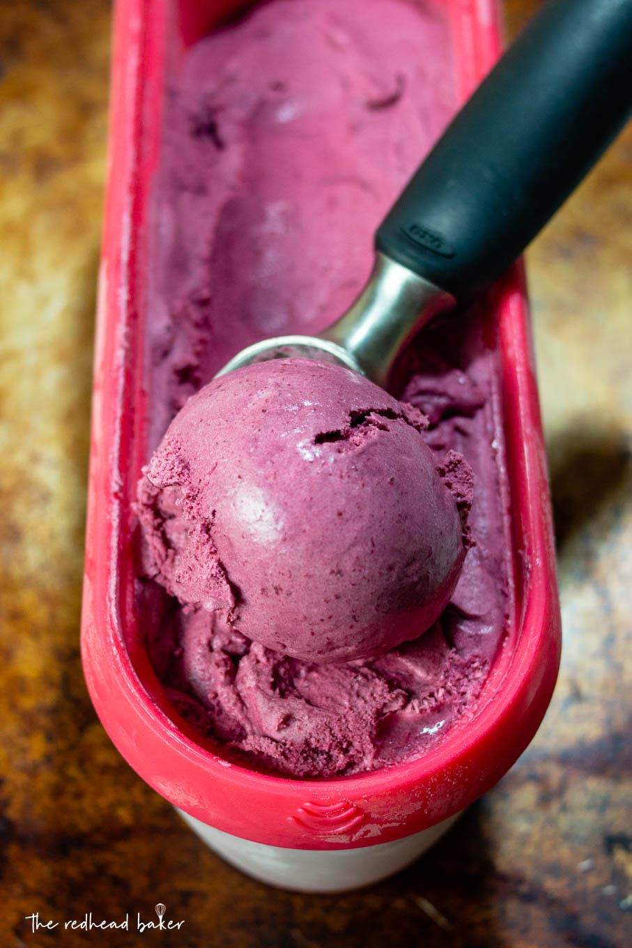 An ice cream scooper in a container of bourbon roasted cherry ice cream