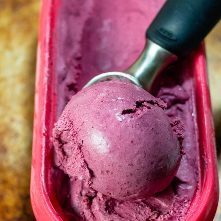 An ice cream scoop in a container of bourbon roasted cherry ice cream