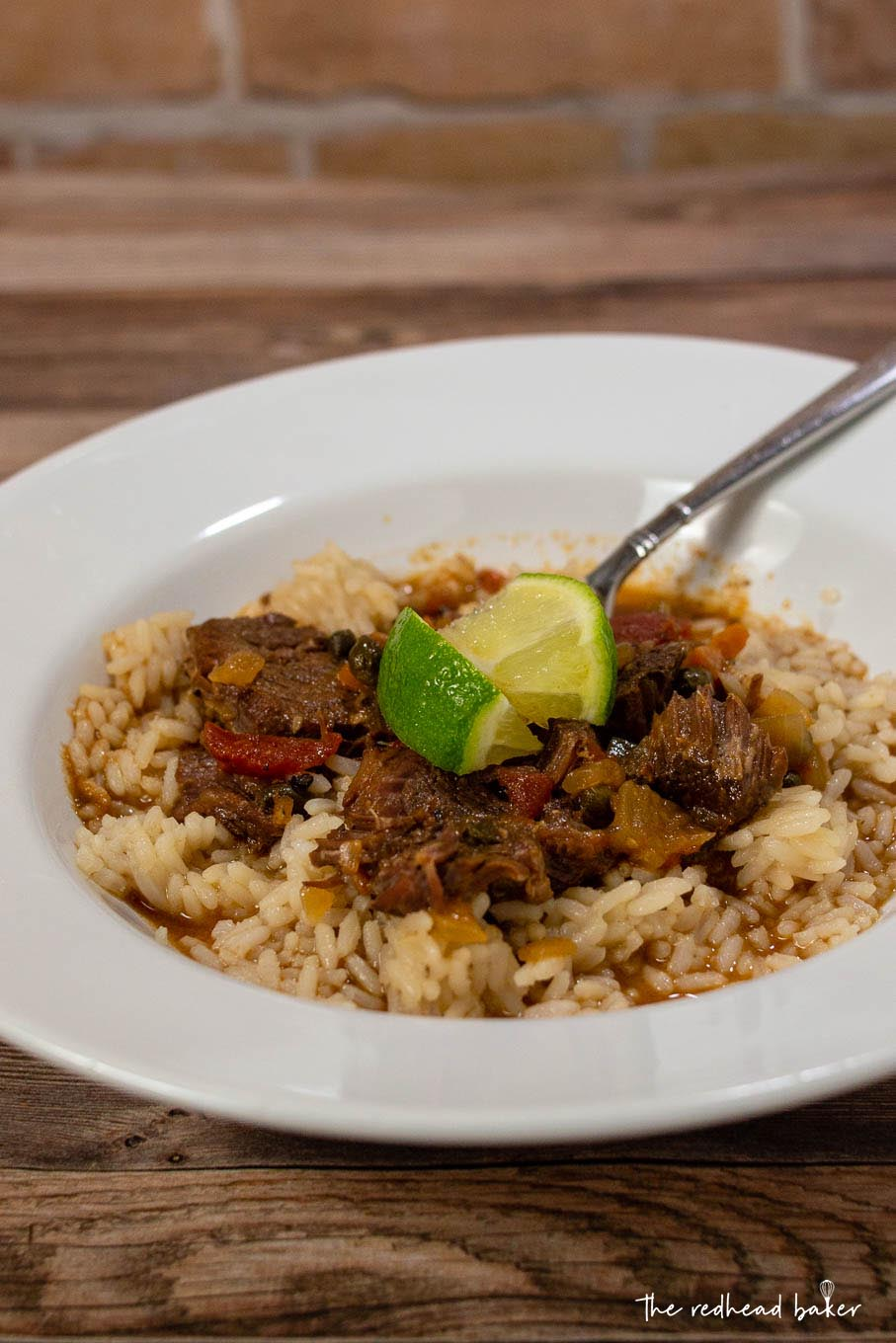 A dish of Cuban Ropa Vieja with lime wedges for garnish
