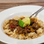 A dish of ropa vieja over rice with lime wedge garnishes