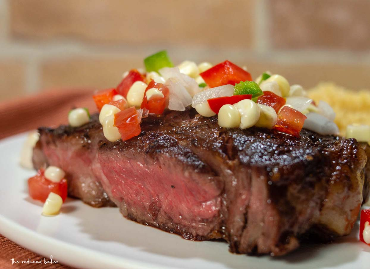 A close-up shot of a ribeye steak topped with corn salsa.