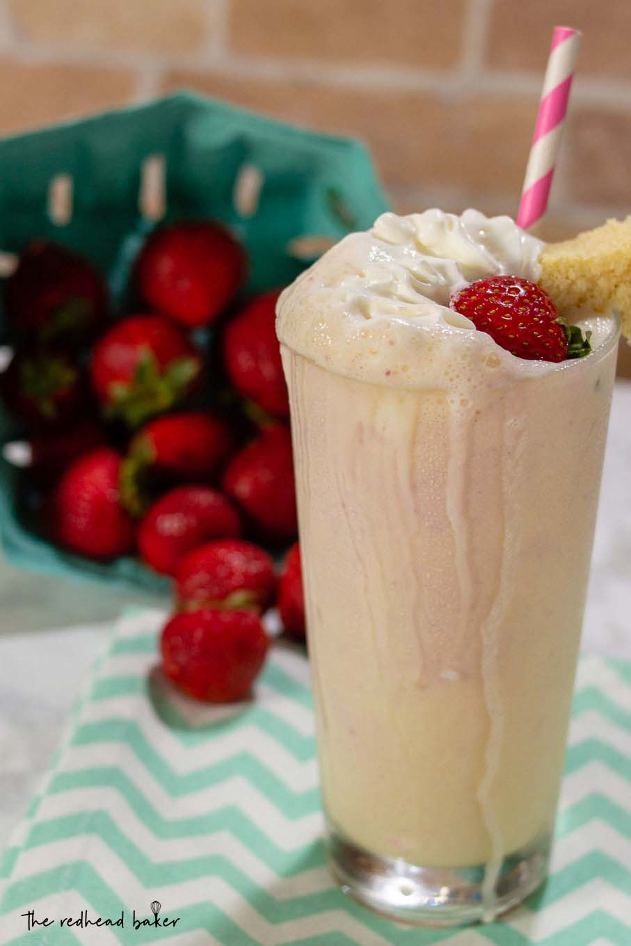 A strawberry shortcake milkshake in front of a tipped carton of fresh strawberries