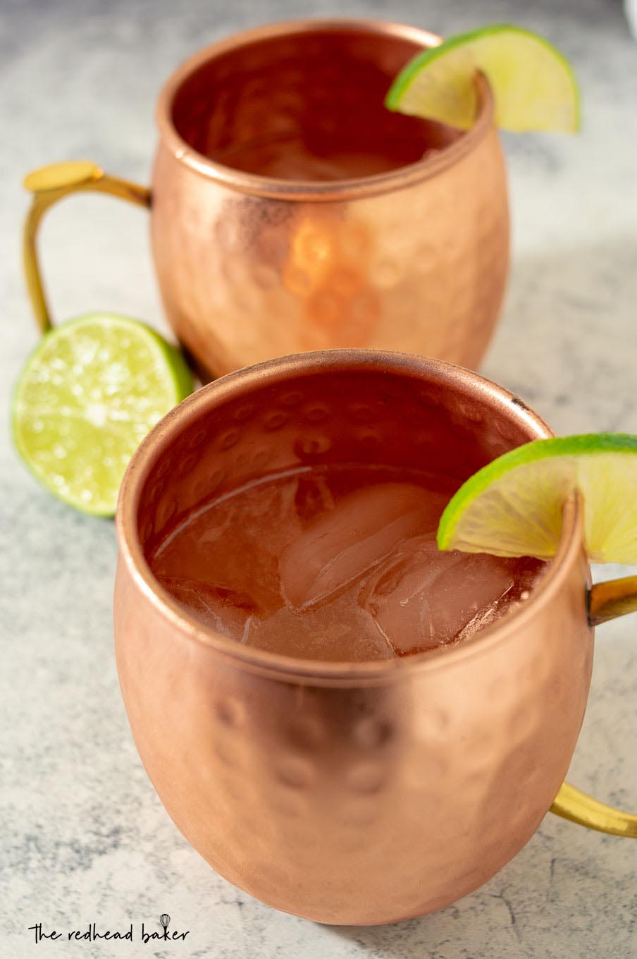 A high-angle shot of two mugs of Apple Cider Moscow Mules