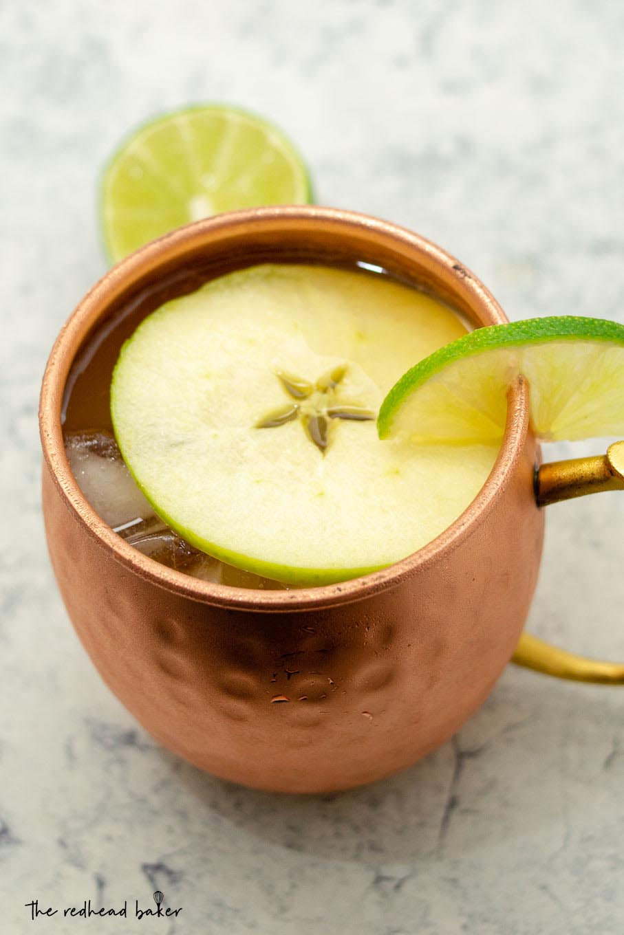 A high-angle shot of an Apple Cider Moscow Mule garnished with a slice of apple