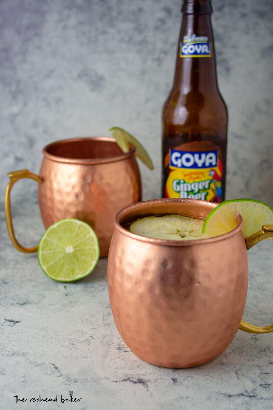 Two mugs of Apple Cider Moscow Mules in front of a bottle of ginger beer