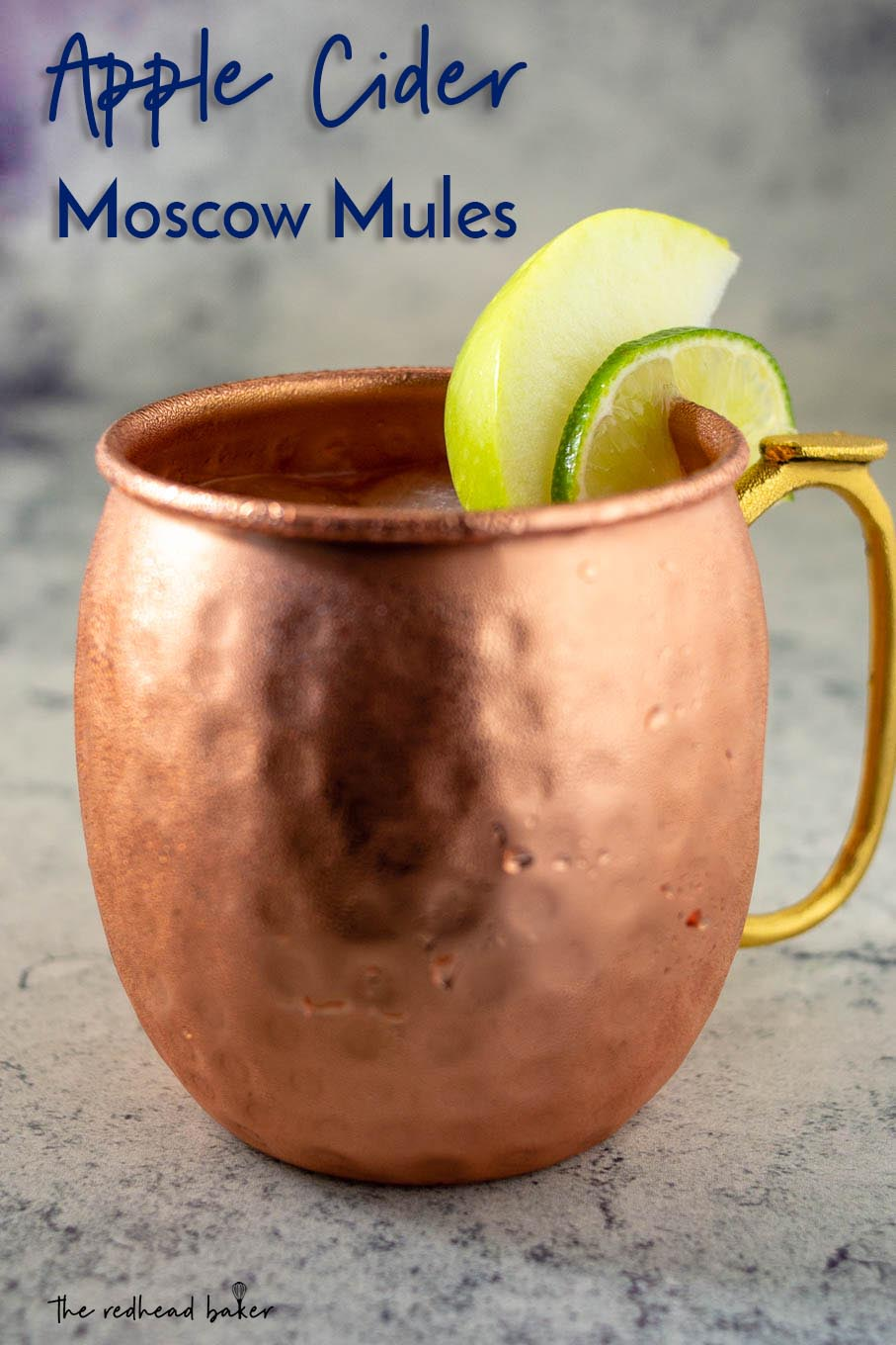 A close-up of a mug of Apple Cider Moscow Mule garnished with an apple wedge and a lime slice
