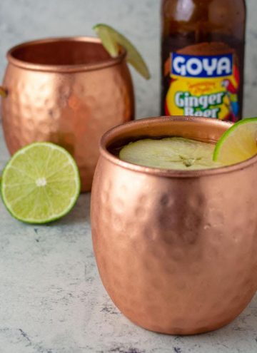 Two mugs of Apple Cider Moscow Mule in front of a bottle of ginger beer