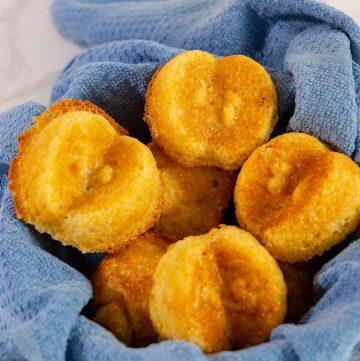 Apple cornbread cakelets in a blue-towel-lined basket