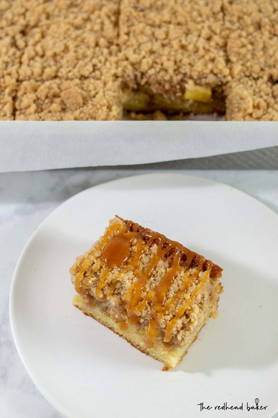A slice of caramel apple crumb cake in front of a cake pan of crumb cake