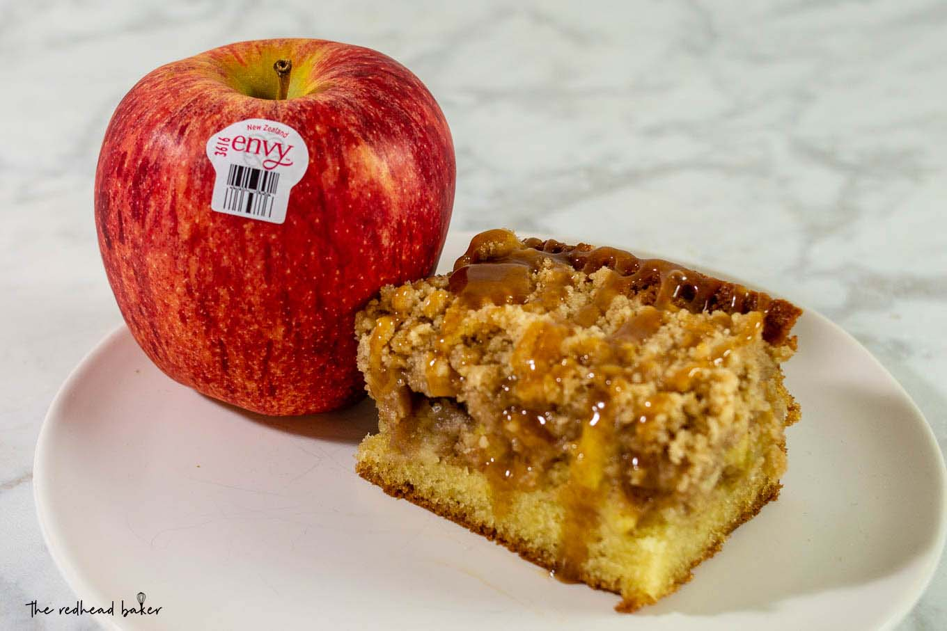 A slice of caramel apple crumb cake next to an Envy apple.
