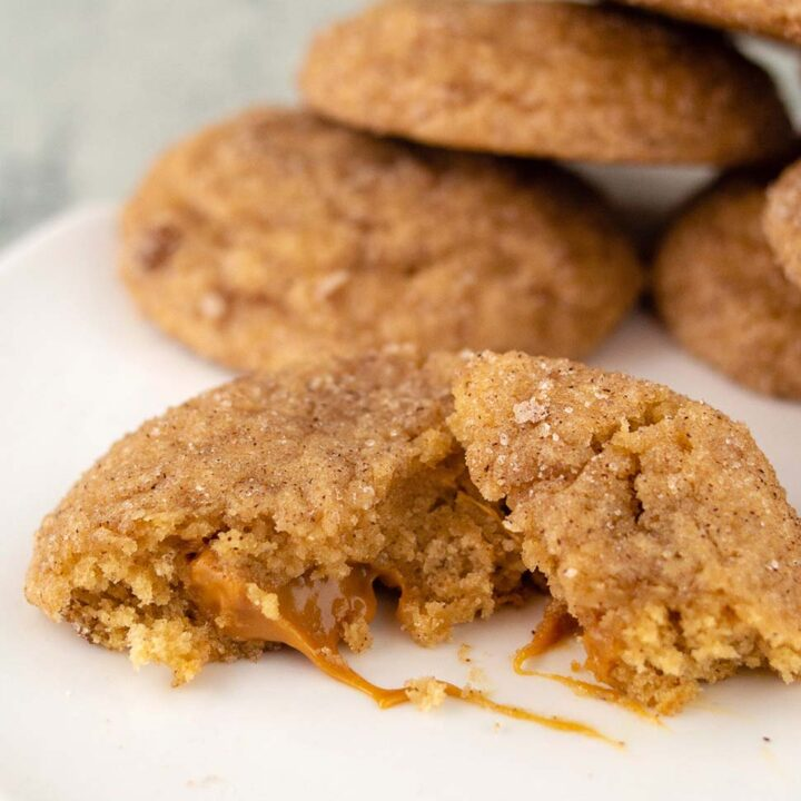 Half of a caramel-stuffed apple butter snickerdoodle with the caramel center oozing out
