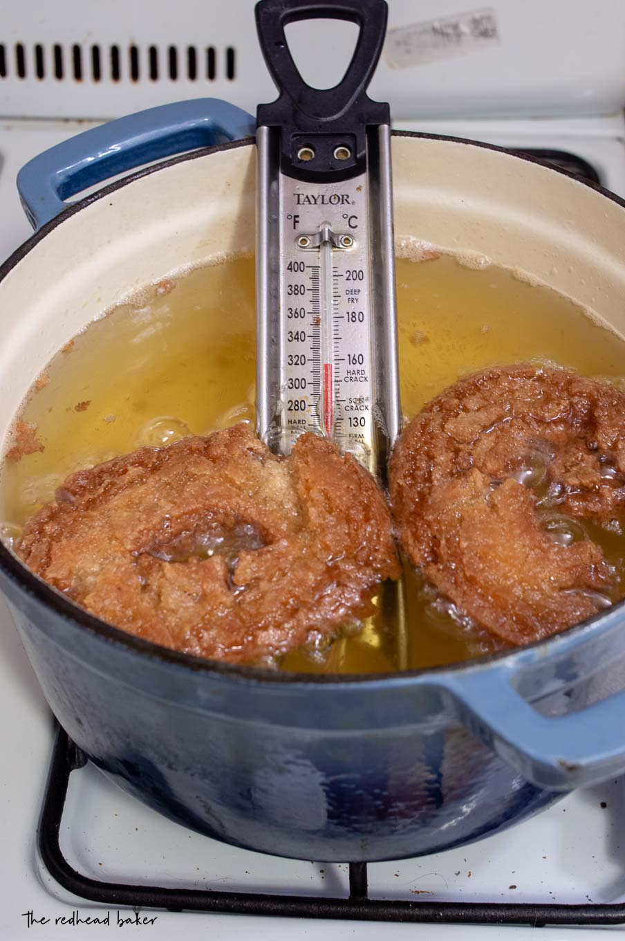 Two cider doughnuts being fried in oil.