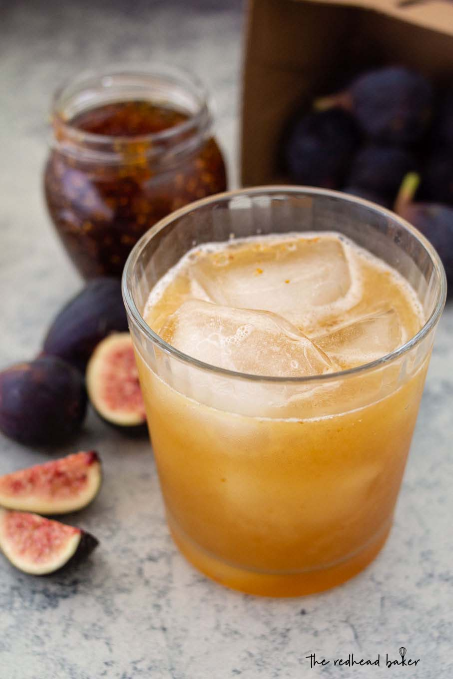 Honey-fig whiskey sour in front of a jar of fig spread and fresh figs