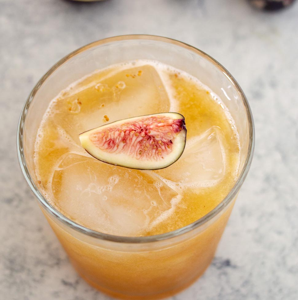 A high-angle shot of a honey-fig whiskey sour garnished with a fresh fig quarter