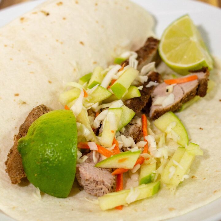 Pork tacos with apple slaw on a plate with lime wedges