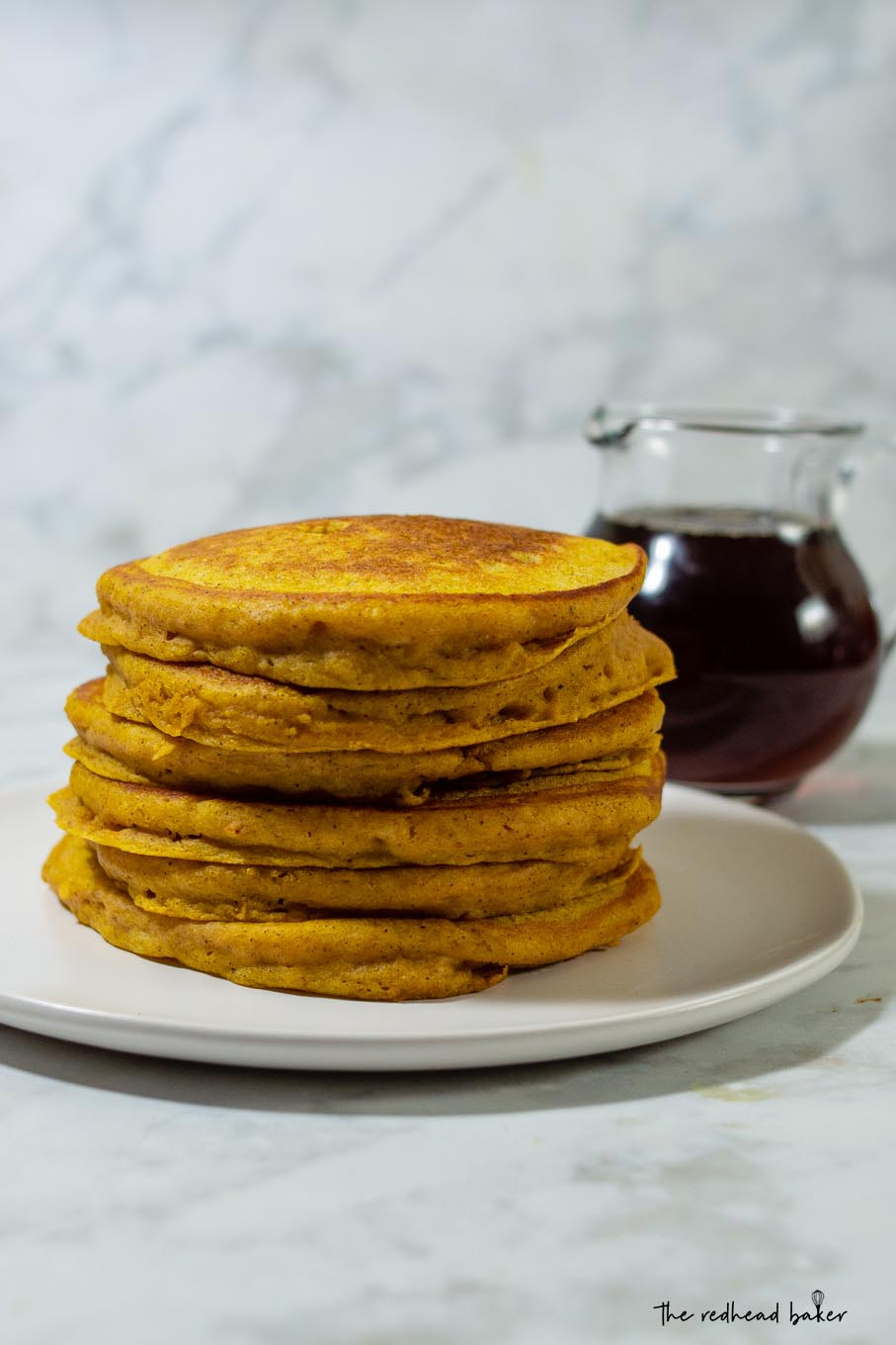 A stack of pumpkin buttermilk pancakes in front of a jar of maple syrup