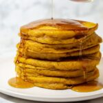 Maple syrup being poured onto a stack of pumpkin buttermilk pancakes