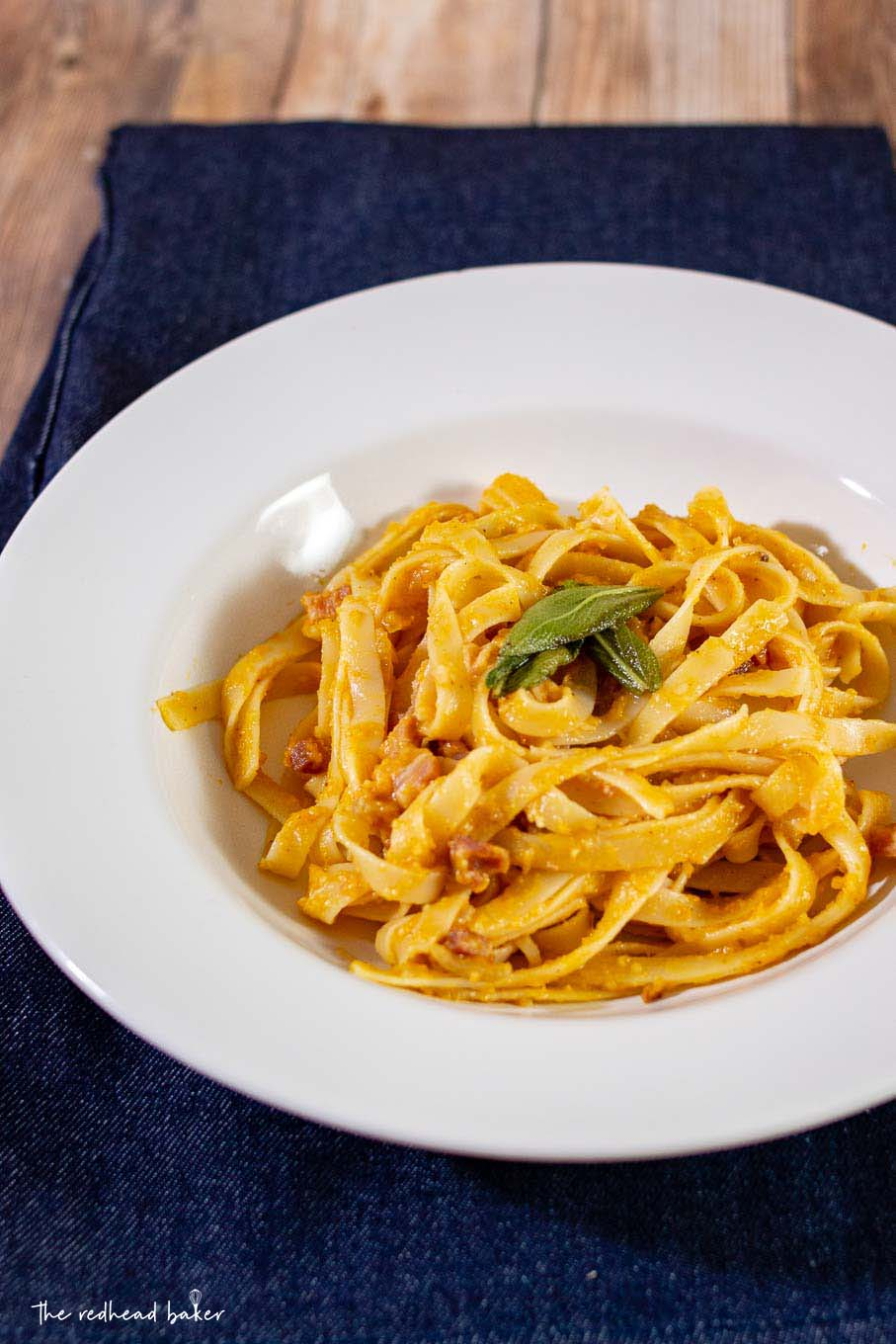 A dish of pumpkin carbonara with fried sage on a blue placemat.