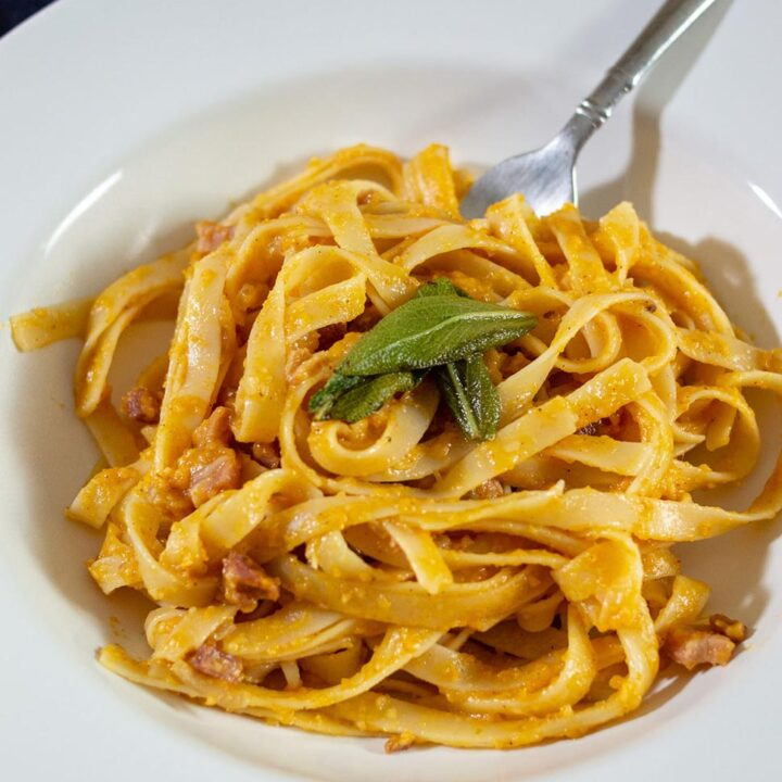 A serving of pumpkin carbonara in a white dish.