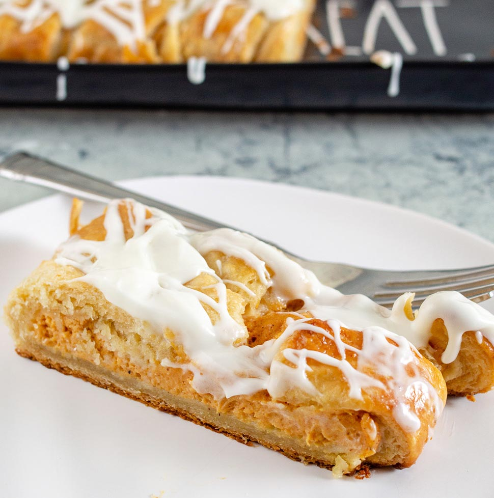 A slice of pumpkin cheesecake danish braid on a white plate in front of a black serving tray with the remaining braid.