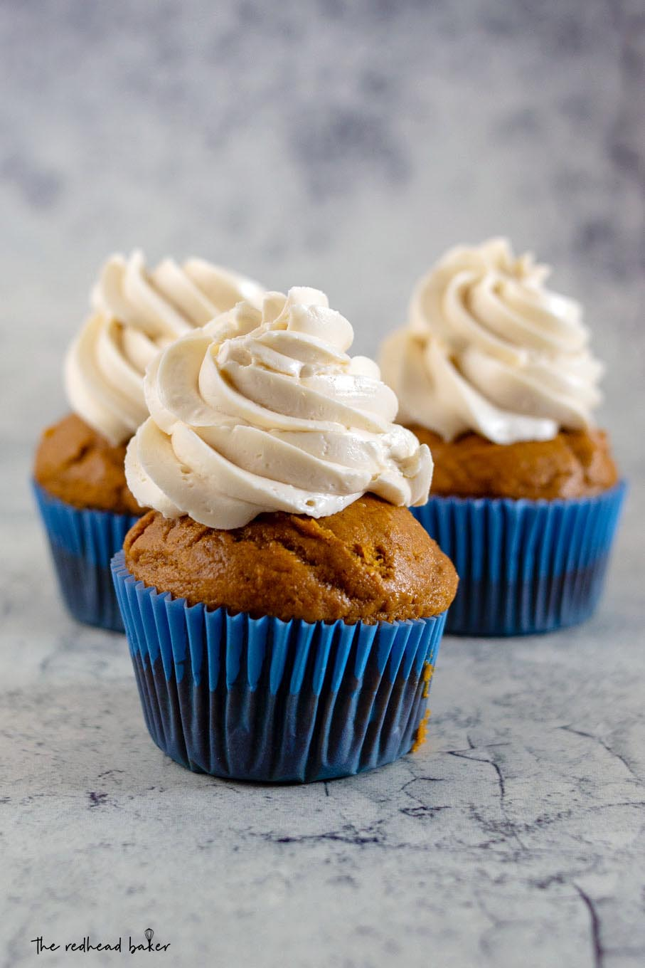 A straight-on view of three pumpkin cupcakes