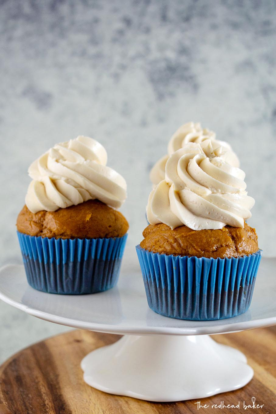 Two pumpkin cupcakes on a white cakestand