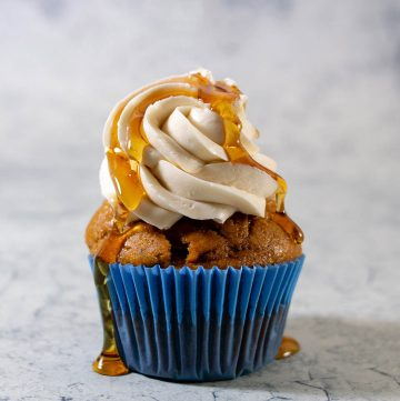 A close-up shot of a pumpkin cupcake with maple syrup dripping down the frosting