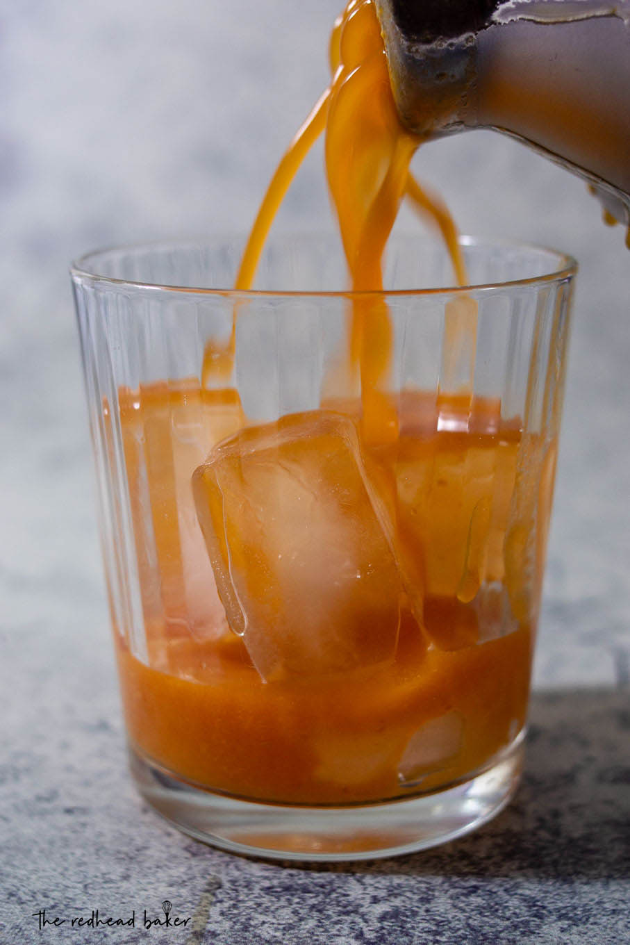 Pumpkin old-fashioned being strained into a glass filled with ice.