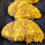 Two caramel-glazed spiced pumpkin scones on a black tray.