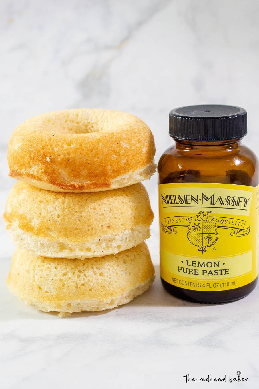 A stack of three baked lemon donuts next to a jar of Nielsen-Massey lemon paste