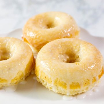 A close-up of three baked lemon donuts with coconut glaze