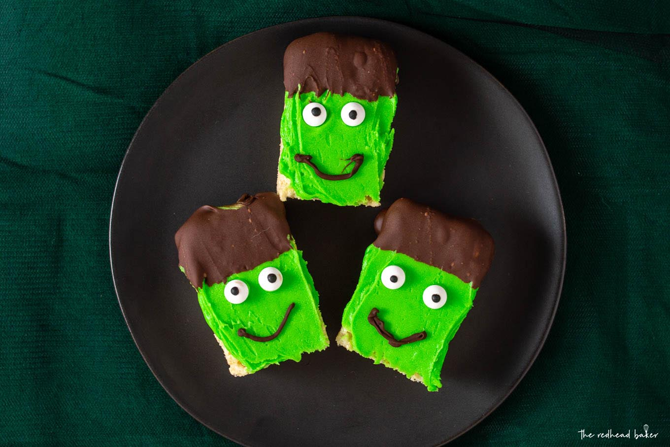 Overhead shot of three Frankenstein Crispy Cereal Treats on a black plate