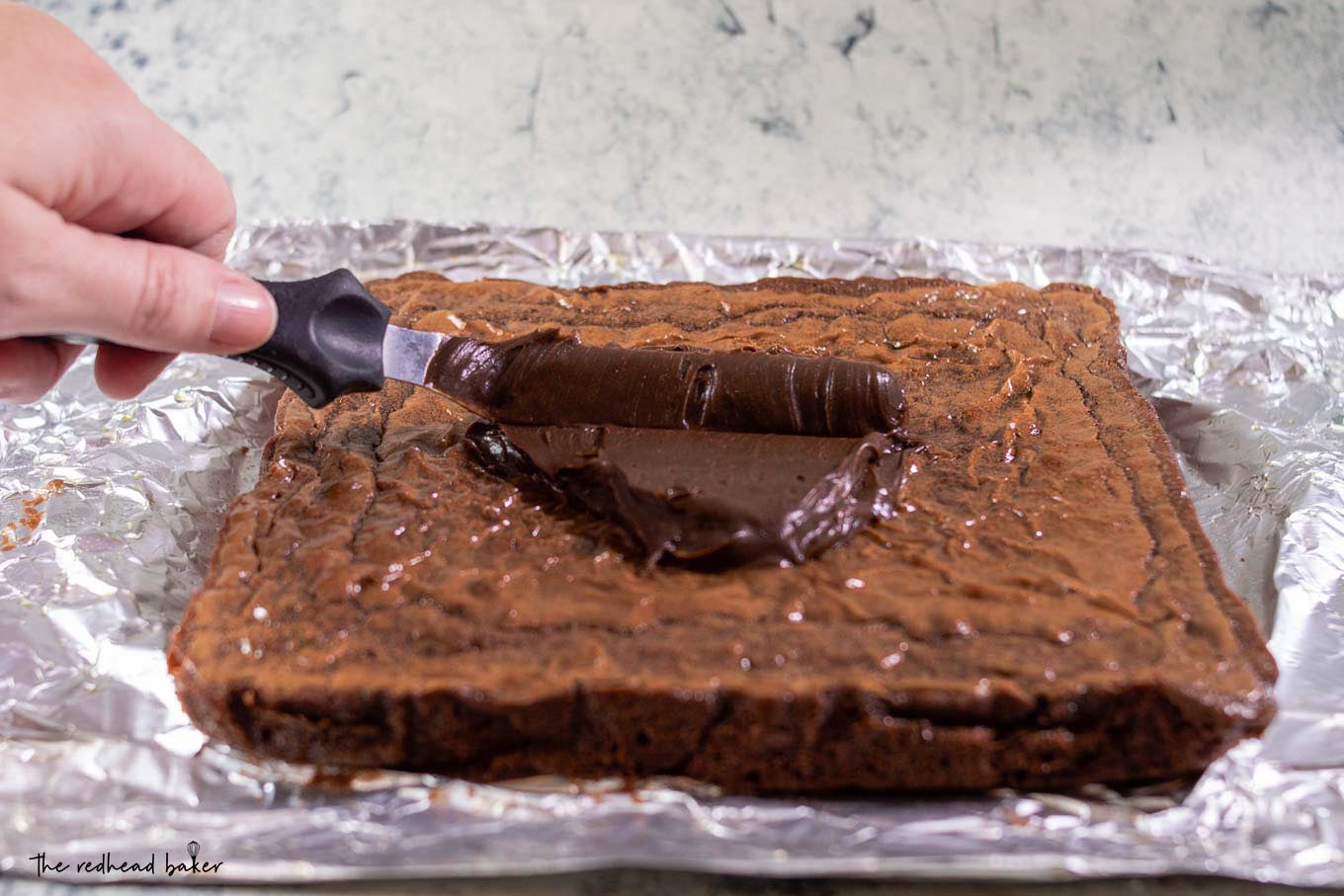 Chocolate icing being spread on a sheet of baked brownies