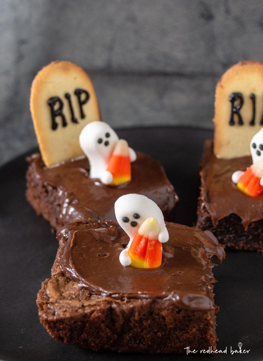 Three haunted graveyard brownies on a black plate