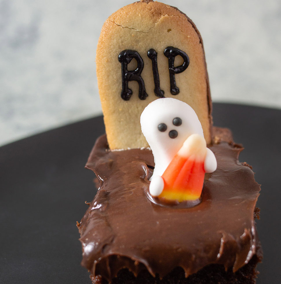 A close-up of a haunted graveyard brownie on a black plate