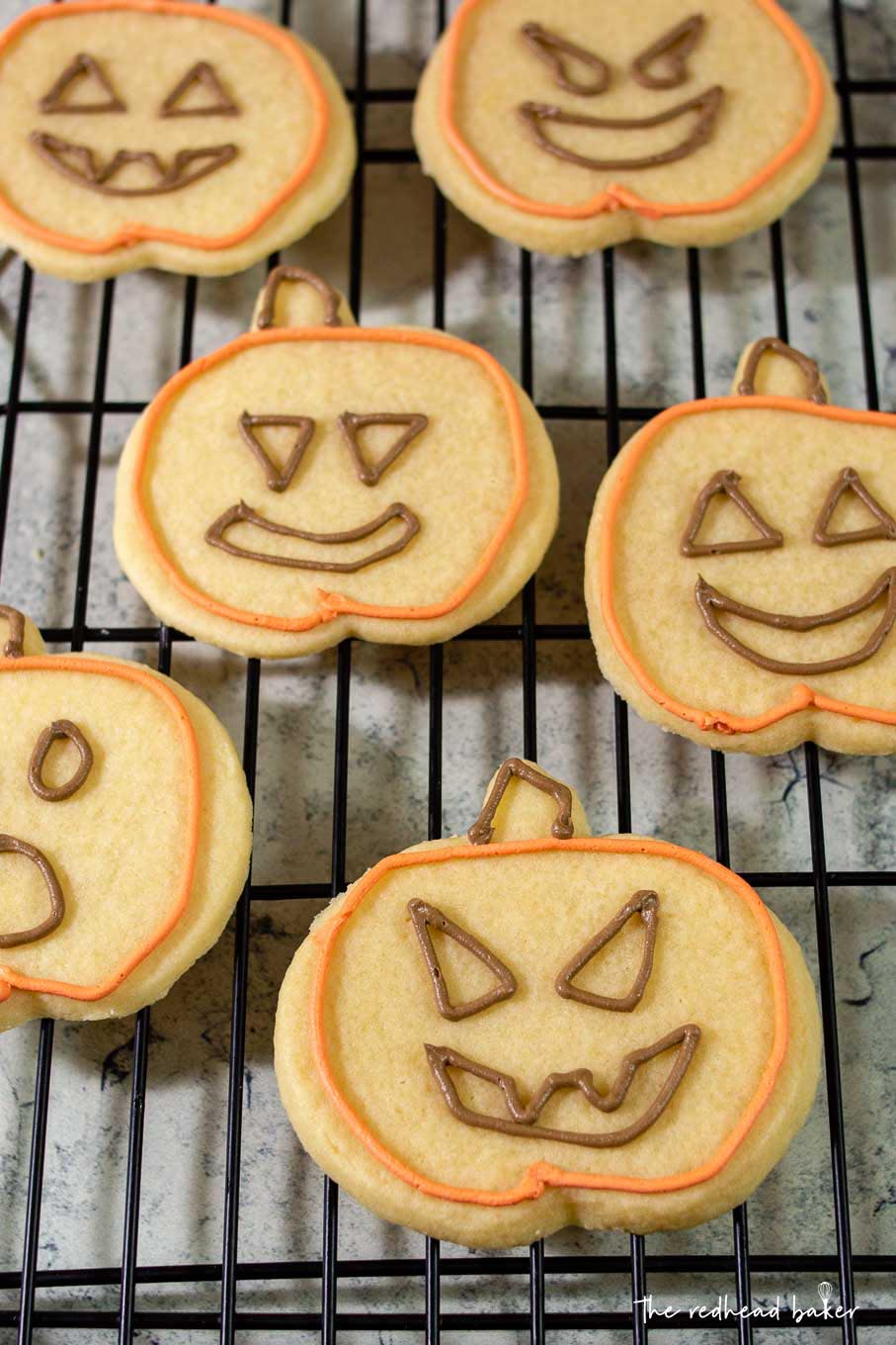 Six jack-o-lantern cookies with orange outlines and brown eyes and mouths