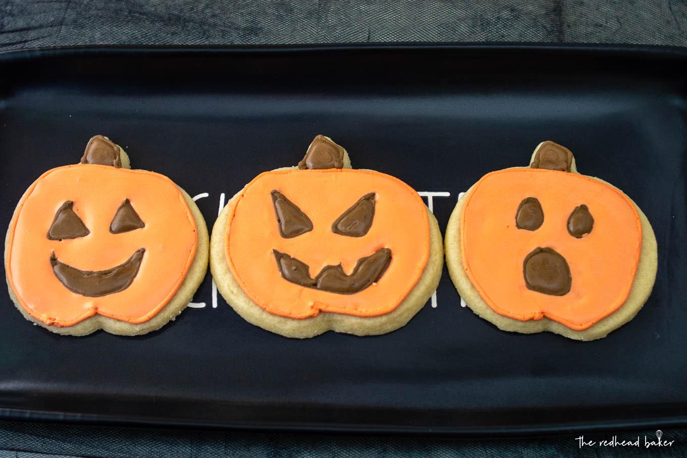 Three jack-o-lantern cookies on a black tray