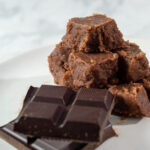 A pyramid of old-fashioned chocolate fudge next to unwrapped squares of Divine Chocolate 100% unsweetened baking chocolate