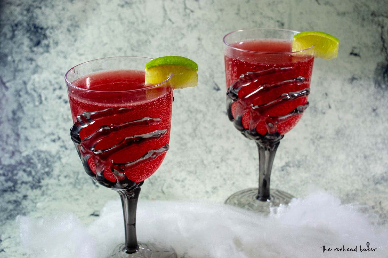 Two glasses of pomegranate margaritas in glasses with skeleton hand stems